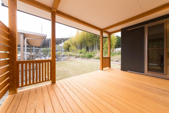 多気郡多気町の注文住宅実例、自然の中に建つ三重の木を使った開放的的な住宅。屋根のあるインナーテラス(ウッドデッキ)があり、リビングの延長空間として中と外をつなぐ。